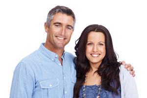 Middle-aged couple standing together smiling l Dental Implants St. Cloud FL