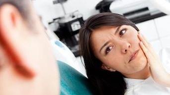 Woman in pain holding face with her hand l Dental Emergency St. Cloud FL